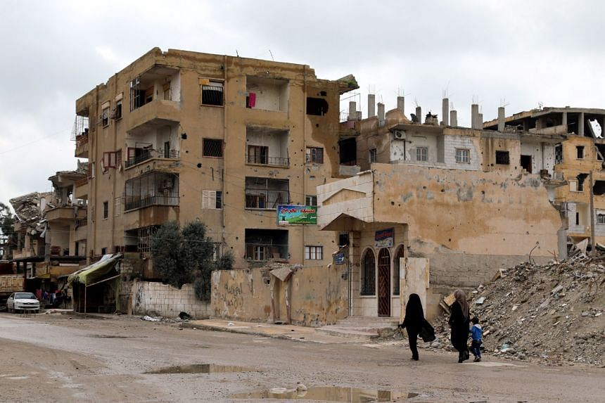 Two Syrian women walk next to destroyed buildings in central Raqqa city.