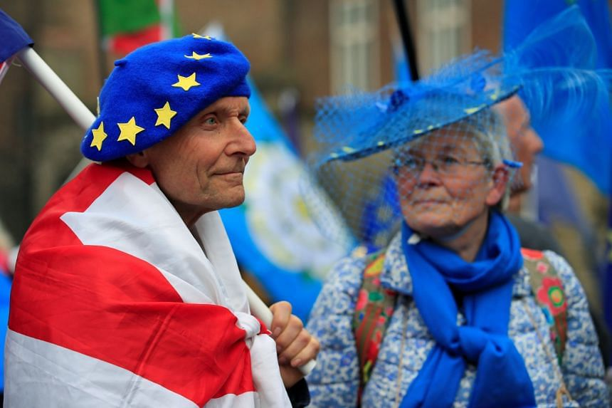Anti-Brexit protesters are seen outside the Houses of Parliament in London.