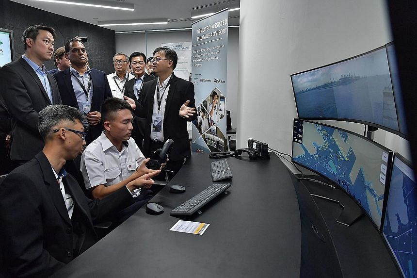 Senior Minister of State for Transport Lam Pin Min (left, standing) being briefed in the Maritime and Port Authority of Singapore's Maritime Innovation Lab yesterday on a remote piloting system that is being developed to allow vessels to be remotely