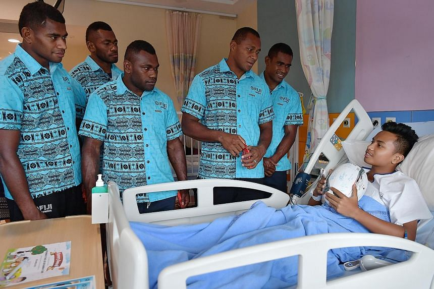 Some of the players from Fiji's rugby sevens team speaking to Syabil Zaini, 14, at the KK Women's and Children's Hospital yesterday. They also gave presents and sang for the patients during their visit ahead of this weekend's Singapore Rugby Sevens a