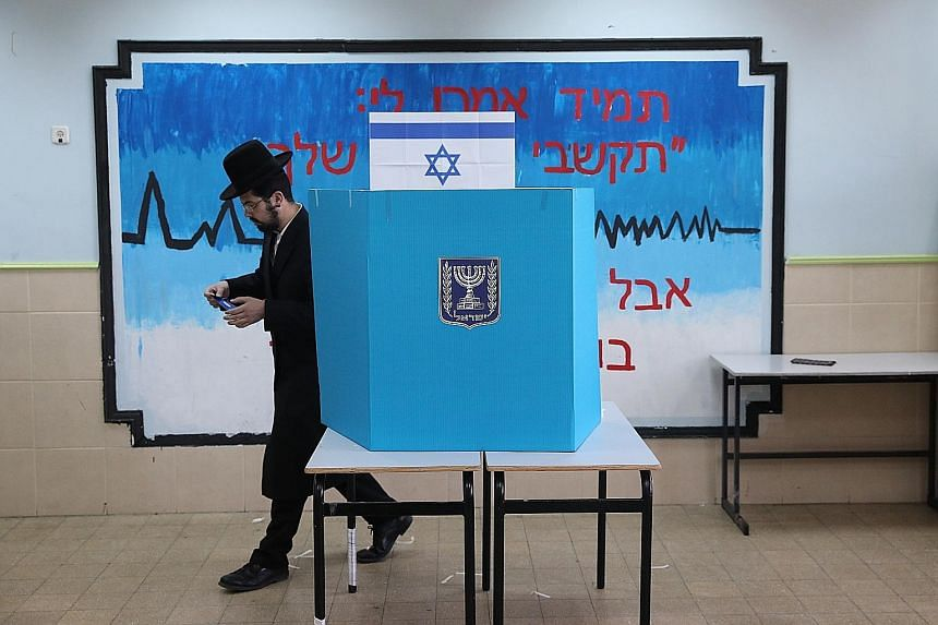 An ultra-orthodox Jewish man casting his vote at a polling station yesterday in Jerusalem, Israel. Nearly 6.3 million Israelis are eligible to vote in the election, which sees Prime Minister Benjamin Netanyahu facing closest rival Benny Gantz, a form