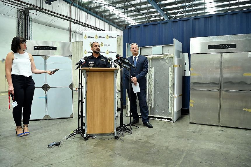Australian Border Force Superintendent Garry Low (centre) and Organised Crime Squad Detective Assistant Superintendent Damian Beaufils with the refrigerators used to hide methamphetamine. The street value of the 585kg of meth is estimated to be more