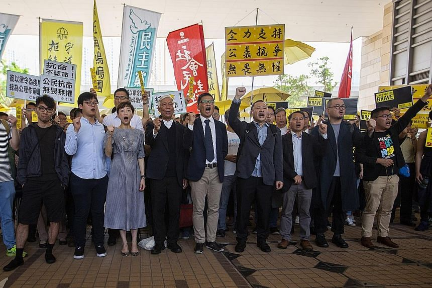 (From left) Eason Chung, Tommy Cheung, Tanya Chan, Chu Yiu Ming, Chan Kin Man, Benny Tai, Lee Wing Tat, Shiu Ka Chun and Raphael Wong in Kowloon yesterday before the court verdict. All nine were behind the massive Umbrella Movement protests centred i