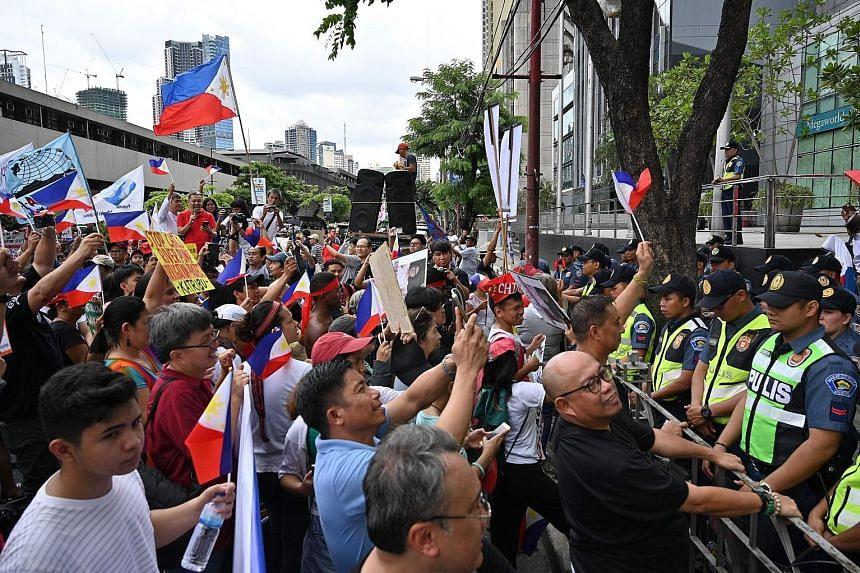 Anti-China protesters raising clenched fists and national flags while shouting slogans during a protest in front of the Chinese embassy in the financial district of Manila yesterday, as policemen stand guard. The marchers, numbering about 1,000, disp