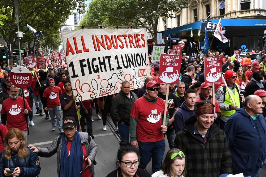 People take part in a march for better work conditions and higher wages in Melbourne, Australia on April 10, 2019.