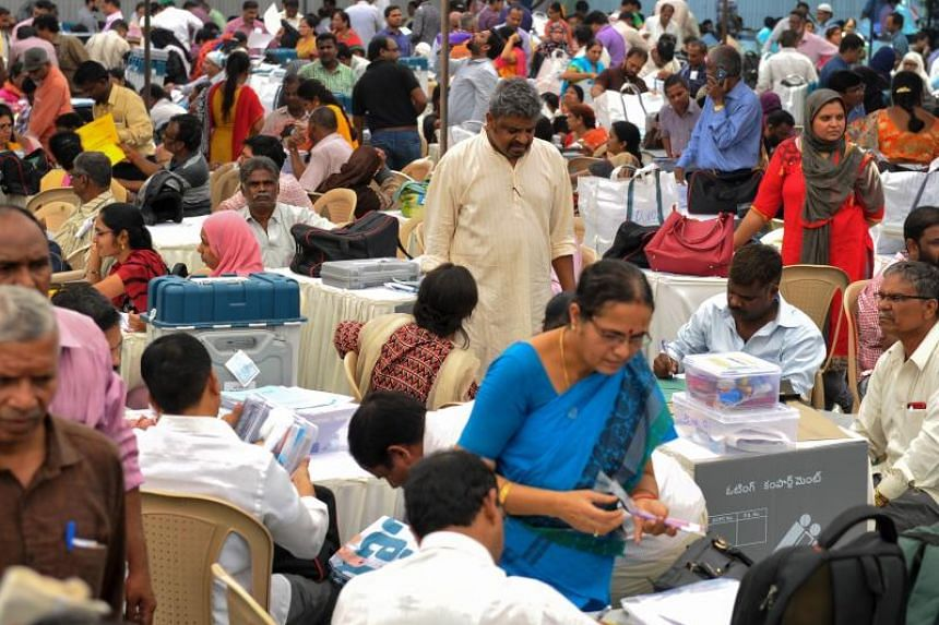 Indian election officials check polling material and Electronic Voting Machines at a distribution centre in Hyderabad on April 10, 2019.