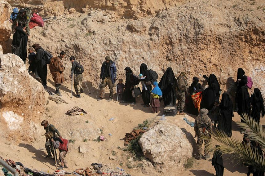 Islamic state fighters and their families walk as they surrendered in the village of Baghouz, Syria, on March 12, 2019.