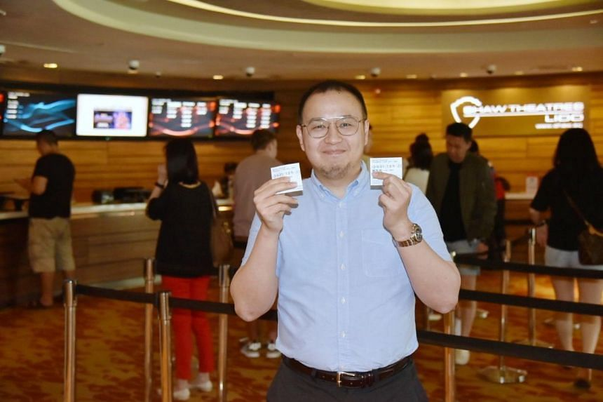 Eric De Leon, 31, analyst, holds up two tickets he bought from the counter at Lido Shaw Theatres during his lunch break.