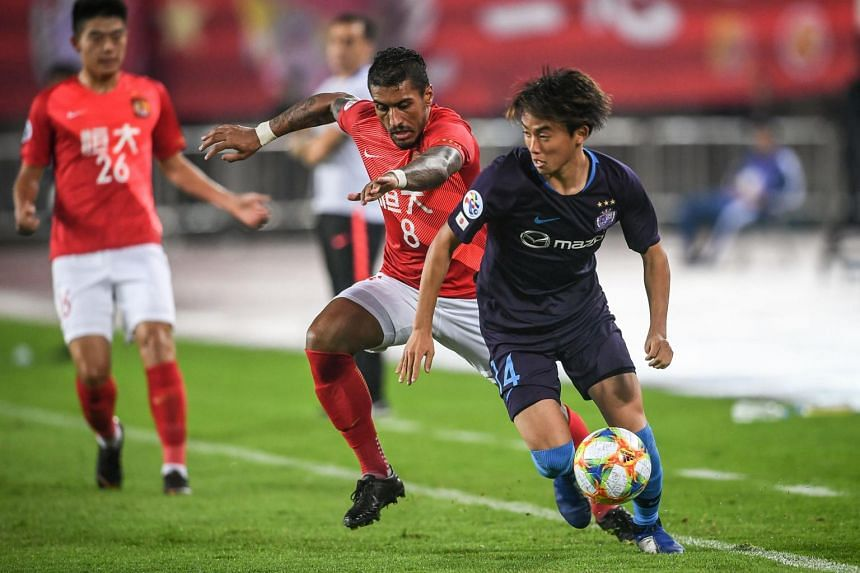 Paulinho (left) of China's Guangzhou Evergrande fights for the ball with Tsukasa Morishima of Japan's Sanfrecce Hiroshima during their AFC Champions League group stage football match in Guangzhou, on March 5, 2019.
