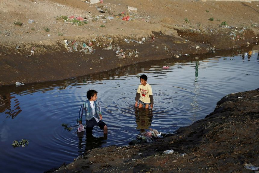 Children play in water at a sewage treatment pool amid an increase of cholera patients in Sanaa, Yemen.