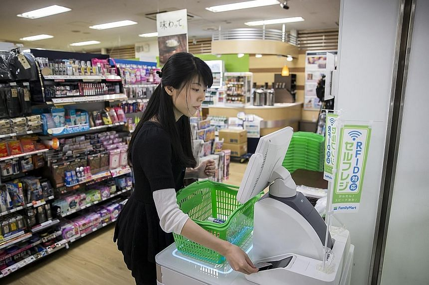 A customer paying for items at an unmanned cash register at a FamilyMart store in Tokyo. FamilyMart, which has more than 16,000 stores in Japan, says it will experiment with reduced-hour operations. It is offering 270 stores the option to join the pr