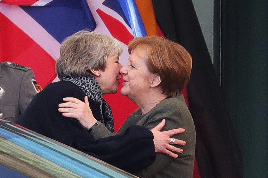 British Prime Minister Theresa May (left) embracing German Chancellor Angela Merkel in Berlin on Tuesday. Mrs May also visited Paris as part of her efforts to win a short delay to Britain's departure from the European Union ahead of an emergency Brex