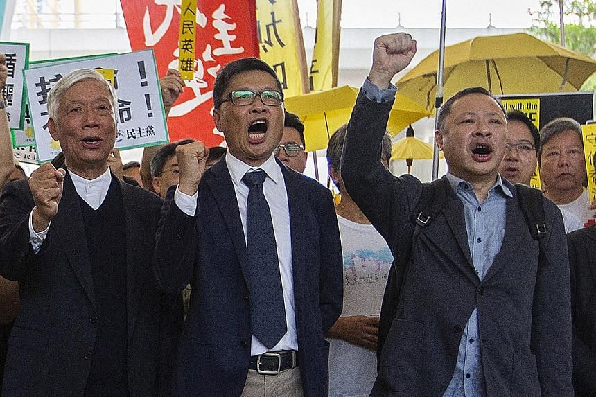 The three prominent leaders behind the Umbrella Movement rallies - (from far left) Baptist minister Chu Yiu Ming, sociology professor Chan Kin Man and law professor Benny Tai - outside the court on Tuesday. PHOTO: EPA-EFE