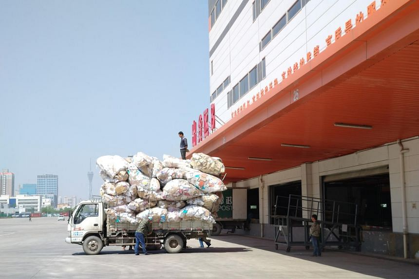Workers loading parcels at a logistics centre in Henan, China, on May 31, 2018.
