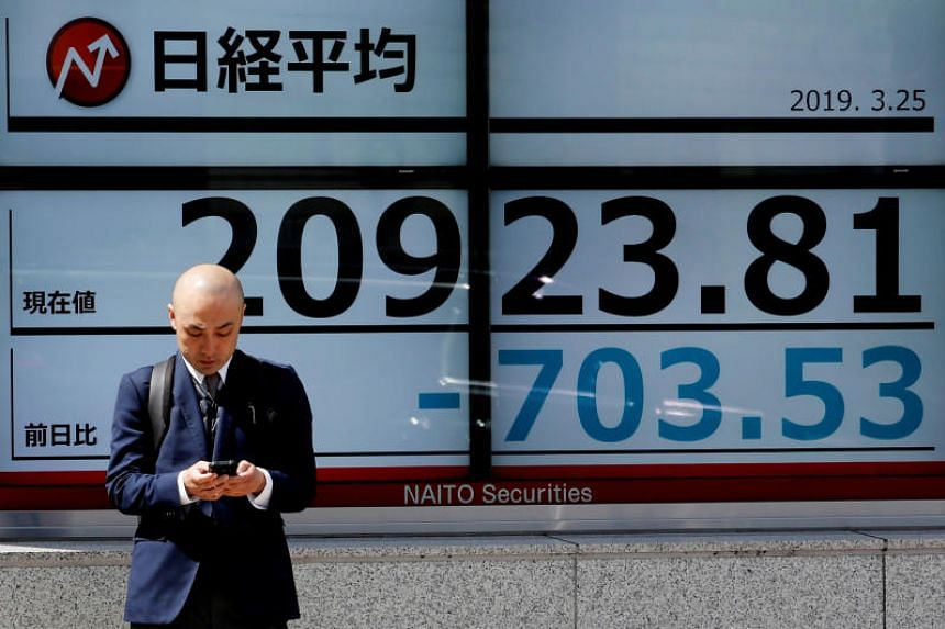 The Nikkei stock index is seen outside a brokerage in Tokyo, on March 25, 2019.