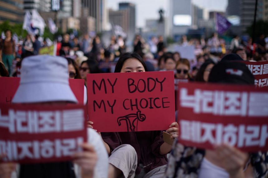 """Protesters hold placards reading """"Abolish punishment for abortion"""" as they protest against South Korean abortion laws in Gwanghwamun plaza in Seoul on July 7, 2018."""