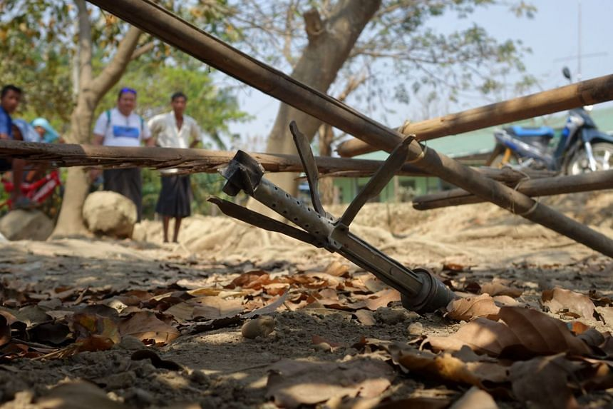 People look at an unexploded rocket in Mrauk U township in Rakhine in March 2019..