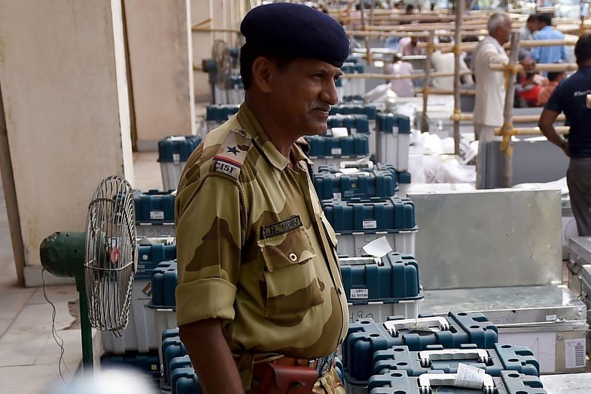 An Indian Central Industrial Security Force officer standing guard near electronic voting machines at a distribution centre in Noida, Uttar Pradesh, yesterday, a day before the first phase of the world's biggest democratic elections.