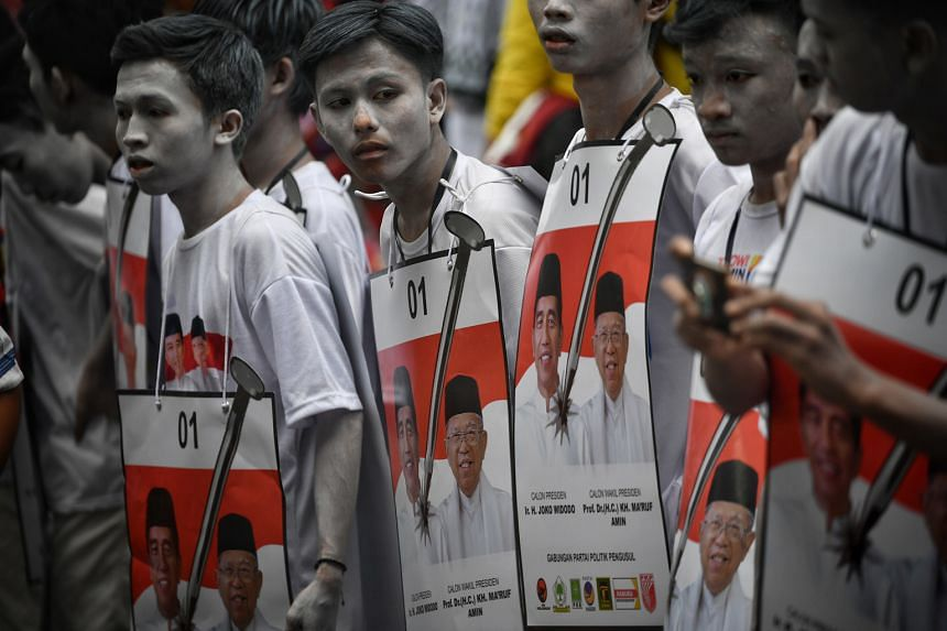 Supporters of President Joko Widodo and his running mate Ma'ruf Amin at a carnival parade in Tangerang Banten on Sunday. Today, Mr Joko will be in Jakarta to prepare for his final election debate. Time