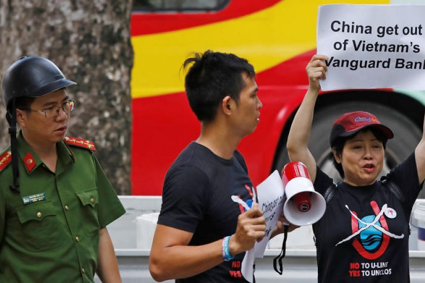 In a photo from Aug 6, 2019, a Vietnamese policeman approaches anti-China protesters as they hold placards during a demonstration in front of the Chinese embassy in Hanoi, Vietnam.