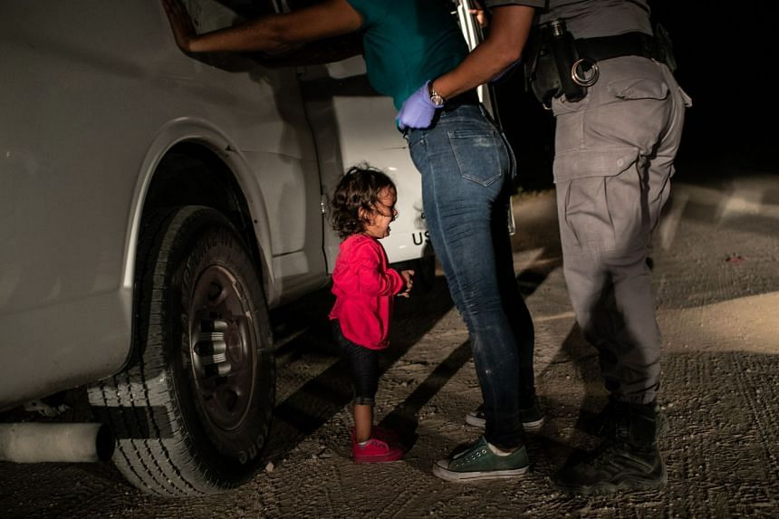 John Moore's photo showing a two-year-old Honduran asylum seeker crying as her mother is searched and detained.