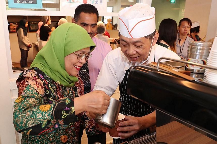 President Halimah Yacob joining senior volunteers who run the SASCO@Khatib Activity Centre's in-house cafe to brew gourmet coffee during her visit yesterday. The centre in Yishun is a community facility that promotes senior learning and volunteerism.