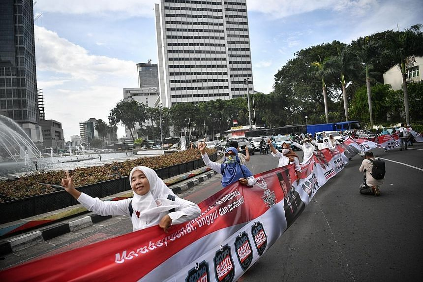 Supporters of presidential hopeful Prabowo Subianto and his running mate Sandiaga Uno parading around the Welcome monument in Jakarta with a 120m-long banner yesterday during the evening rush hour. ST PHOTO: ARIFFIN JAMAR