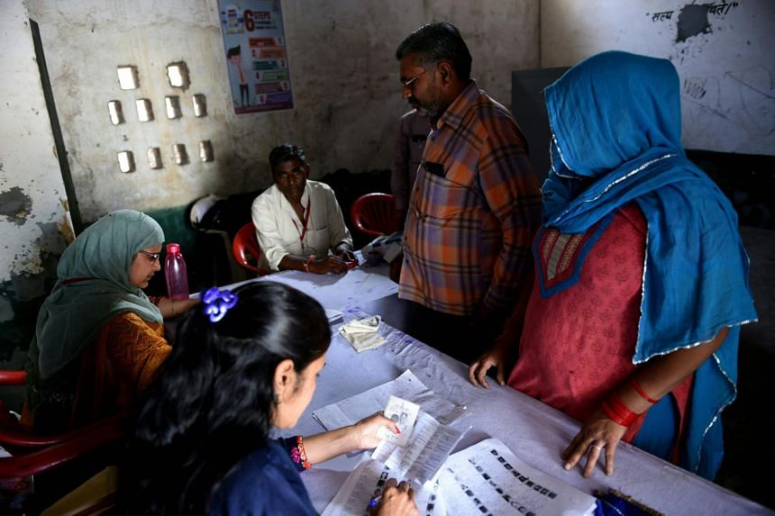 An Indian couple check their names before casting their vote at a polling station during India's general election in Uttar Pradesh. In India, anyone who is over 25 and does not have a criminal conviction can stand in the election.
