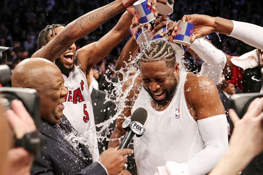 Above: LA Clippers' Montrezl Harrell dunking in the 143-137 home win over the Utah Jazz on Wednesday. Left: The retiring Miami Heat veteran Dwyane Wade being doused with water after his last game at the Brooklyn Nets.