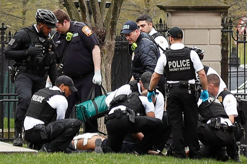 Police and rescue personnel remove a man on a stretcher from Lafayette Park after the man lit his jacket on fire in front of the White House.