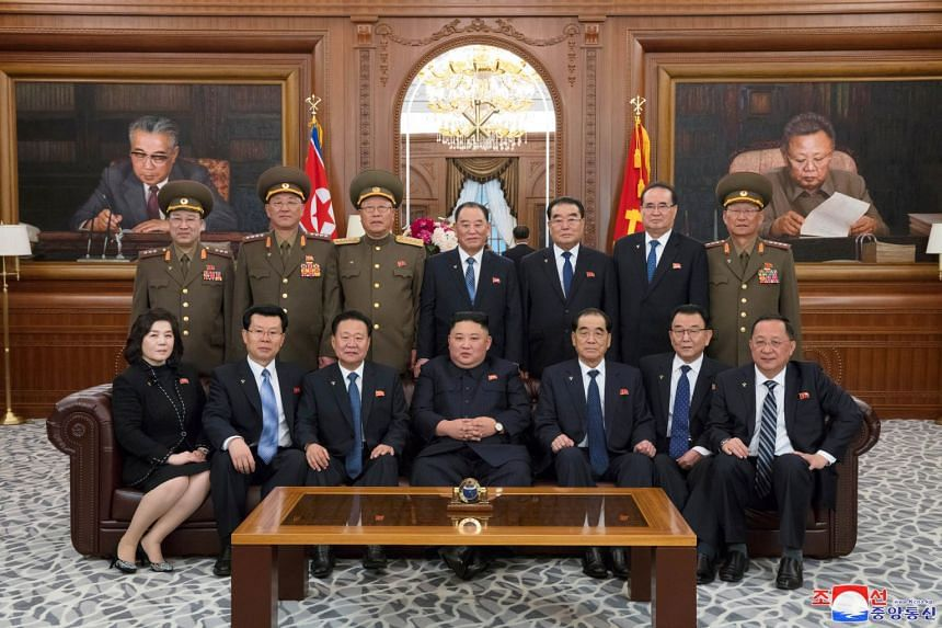 Kim (centre, bottom row) poses for a picture with delegates as he attends the 14th Supreme People's Assembly.