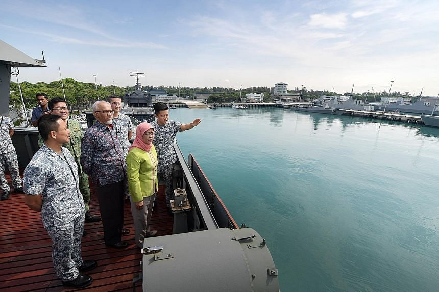 President Halimah Yacob and her husband Mohamed Abdullah Alhabshee being given an overview of the RSS Singapura - Changi Naval Base from the landing ship tank RSS Endeavour by Captain Yeo Shuang Xuan, the ship's navigation officer, accompanied by Chi
