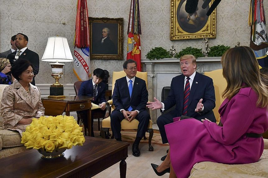 US President Donald Trump and First Lady Melania Trump (her back facing camera) meeting South Korean President Moon Jae-in and his wife, Ms Kim Jung-sook, in the Oval Office at the White House on Thursday. PHOTO: AGENCE FRANCE-PRESSE