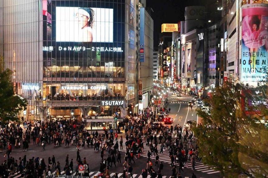 People walking across the landmark pedestrian crossing in Tokyo's Shibuya district, on April 6, 2019.