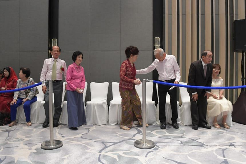 Couples line up to receive their commemorative wedding certificates at the Golden Jubilee Wedding Celebrations at the Fairmont ballroom of the Raffles City Convention Centre.