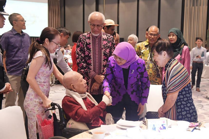 Mr Kang Tian Chan, 88, shakes hands with President Halimah Yacob, as his wife of 57 years, Mdm Khoo Swee Tin (right), looks on.