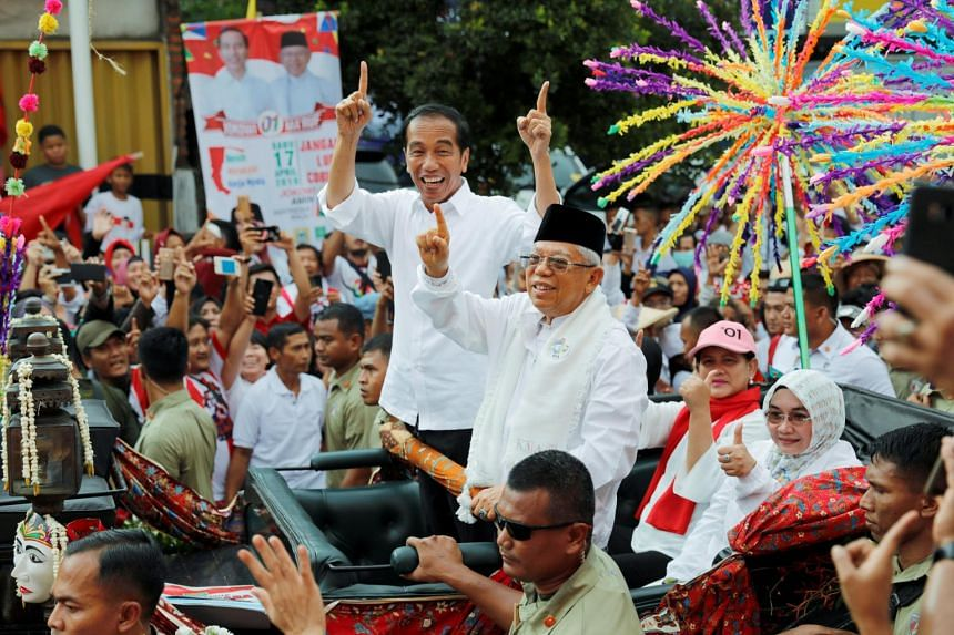 Indonesia's President and presidential candidate for the next election Joko Widodo and his running mate Ma'ruf Amin gesture as they greet their supporters at a carnival during a campaign rally in Tangerang, Banten province, on April 7, 2019.