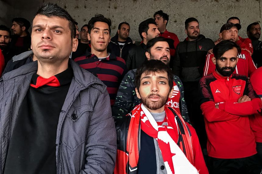 A woman disguised as a man at a football match at Teheran's Azadi Stadium. In Iran, women have been banned from attending men's football matches since 1980. This photo won first prize in the Sports (Stories) category.