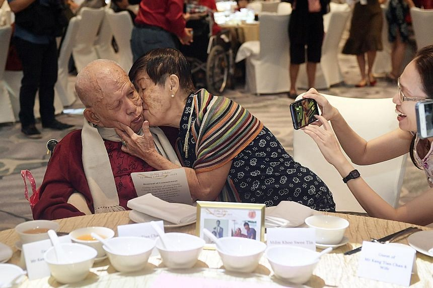 Mr Kang Tian Chan, 88, receiving a kiss from his wife of 57 years, Madam Khoo Swee Tin, who is in her late 70s. They were at the Golden Jubilee Wedding Celebrations, co-organised by the Registry of Marriages and the Registry of Muslim Marriages, yest