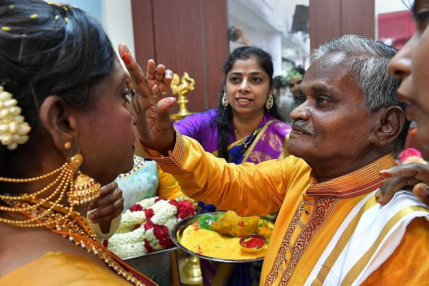 Above: Mr Velappan Vellayan applying red powder onto Madam Savithiri Kaliappan's forehead during the traditional Hindu wedding ceremony at Sree Narayana Mission Nursing Home on Friday. Right: Volunteers from the Cycling Without Age initiative prepari
