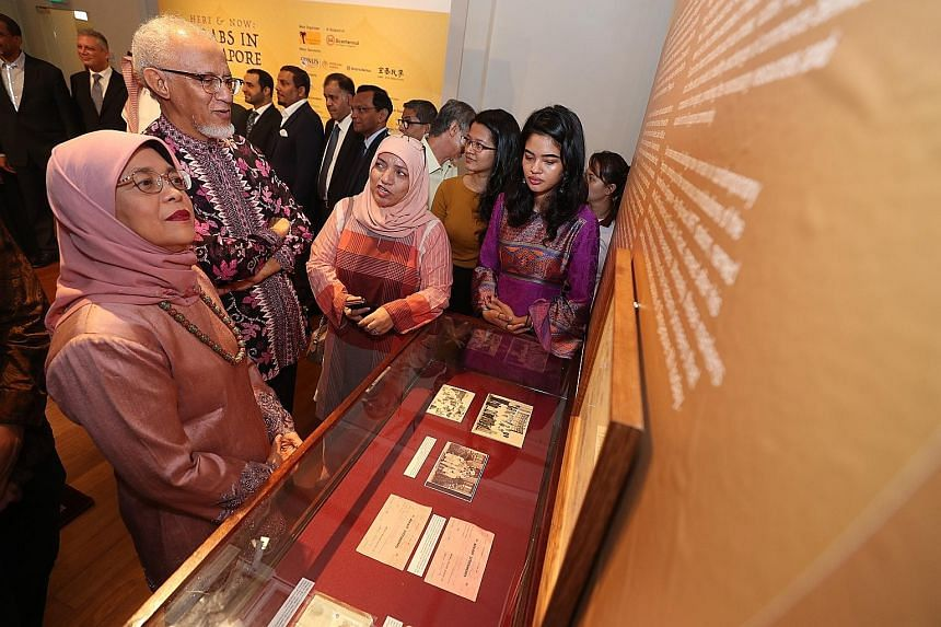 President Halimah Yacob and her husband, Mr Mohamed Abdullah Alhabshee - who is of Arab descent - being briefed on the exhibits at the Here And Now: Arabs In Singapore exhibition at The Arts House yesterday.