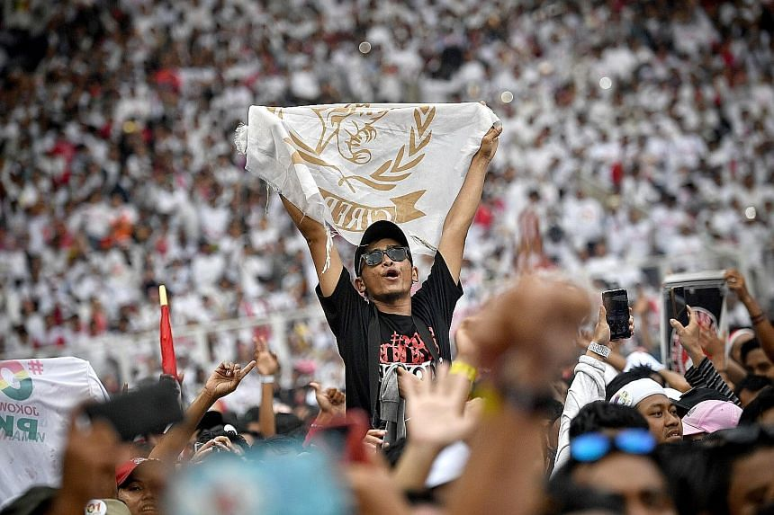 A supporter raising a flag during a concert at President Joko Widodo's final campaign rally yesterday in Jakarta. ST PHOTO: ARIFFIN JAMAR