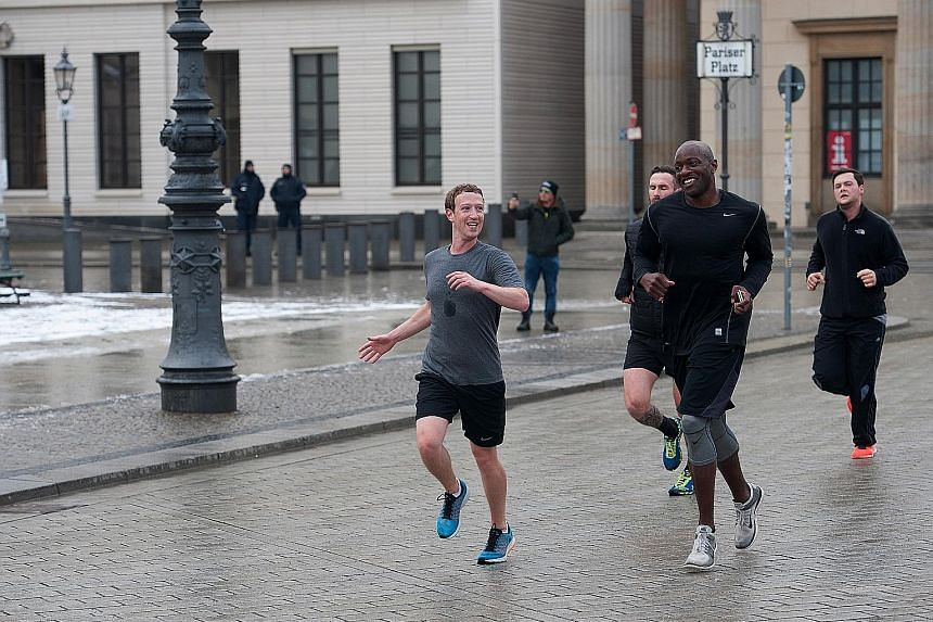 Facebook founder and chief executive Mark Zuckerberg (left) running across Pariser Platz with bodyguards in Berlin, Germany, in February 2016. The company more than doubled the money it spent on his security last year, of which nearly US$20 million w