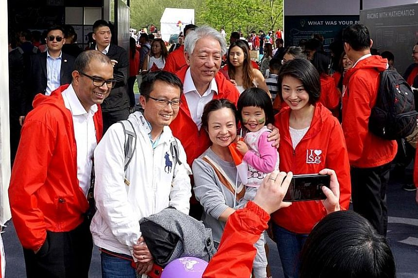 Deputy Prime Minister Teo Chee Hean, Senior Minister of State Janil Puthucheary and Senior Parliamentary Secretary Sun Xueling with Singapore Day participants yesterday.