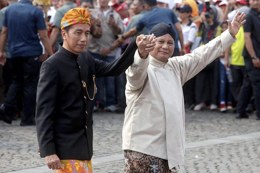 Indonesian President Joko Widodo (left) and his challenger in this year's presidential election, Prabowo Subianto, walk hand-in-hand during an event held in Jakarta, on Sept 23, 2018.