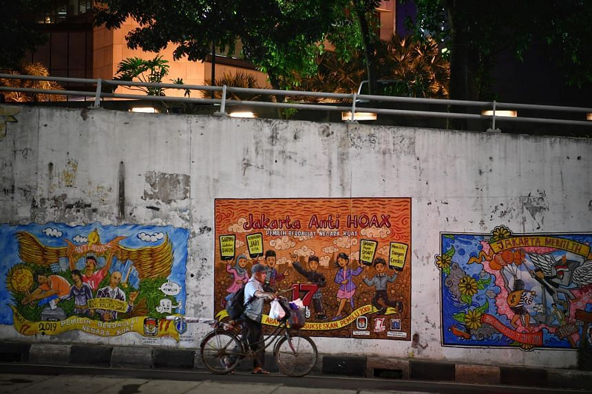 A man in downtown Jakarta pushing his bicycle past a series of election-related murals, including one with an anti-hoax message. The 2019 elections have been hit by a string of fake news. Indonesia's Ministry of Communication and Information Technolo