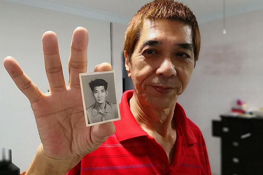 Mr Sim Eng Sua holding a photo of his father, Mr Sim Toh Hock, who has not returned to their Bukit Panjang flat or contacted his family since heading out for breakfast on the morning of Aug 4, 2004.