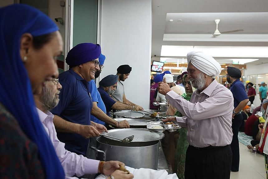 Minister for Communications and Information S. Iswaran (third from left), Sikh Advisory Board chairman Surjit Singh (second from left) and former MP Inderjit Singh (fifth from left) serving dinner to members of the Sikh community at the Central Sikh