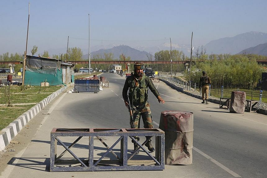 A soldier guarding Kashmir's Srinagar-Jammu highway on April 7. The government has banned civilian movement on the highway two days a week for the safe passage of Indian security convoys.