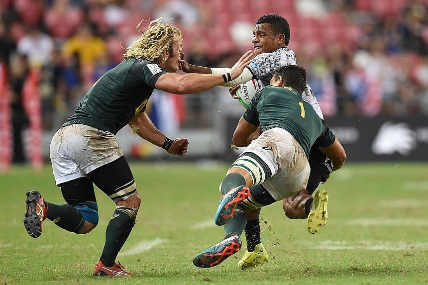 Left: Fiji's Napolioni Bolaca trying to fend off South Africa's Werner Kok (far left) and Chris Dry in the HSBC Singapore Rugby Sevens Cup final yesterday at the National Stadium. Below: The South African team celebrating their second win in the last